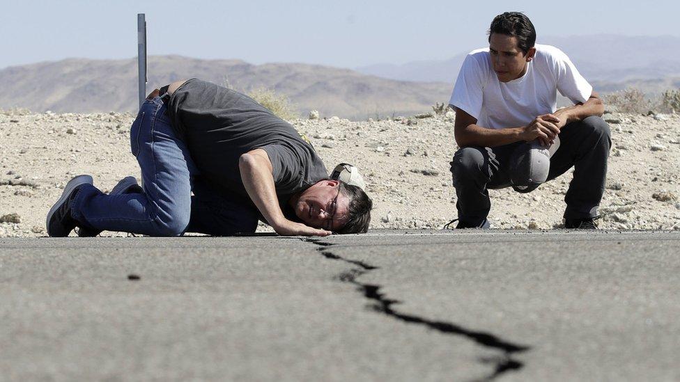 Hombres sobre las rajaduras en las rutas en California tras el terremoto.