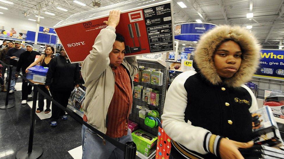 Personas cargan productos en un Black Friday.