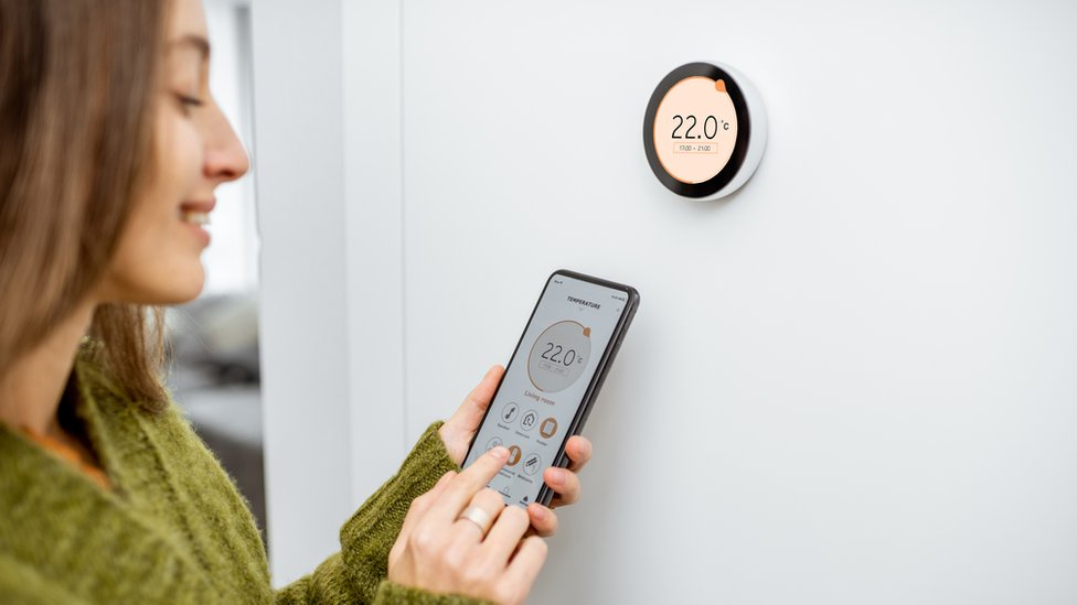 A woman interacts with the Google Nest smart thermostat on a wall
