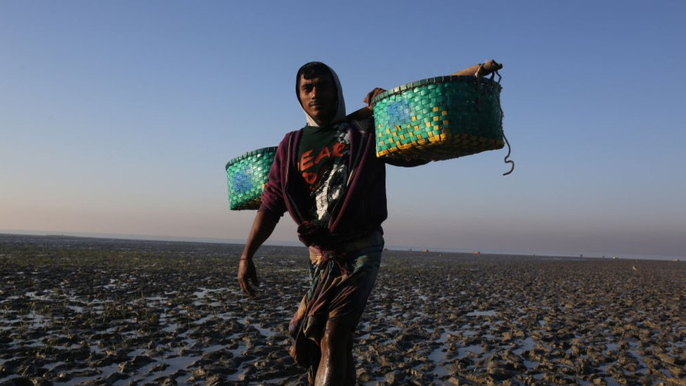 Fisherman carries fish, walks along a muddy beach to sell them at a market in Chittagong, Bangladesh on January 7, 2019.