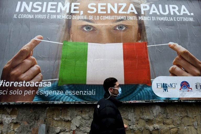Napoli sokaklarında yürüyen maske takmış bir İtalyan