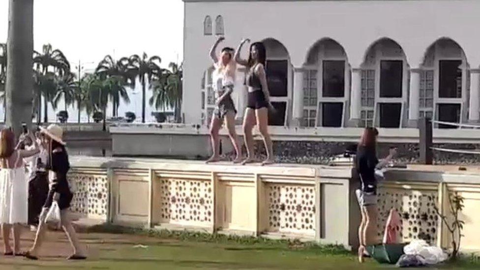 Two women dancing in front of the Kota Kinabalu City Mosque, Malaysia