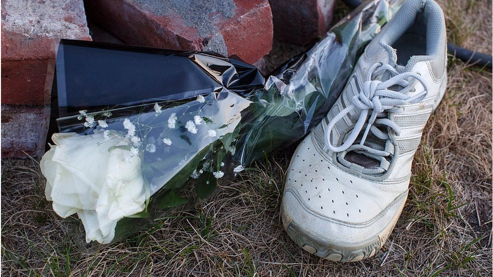 A running shoe and white rose at a memorial