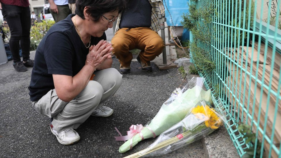 Japan's Yasuko Atsukata, who witnessed the crime scene where a man stabbed 19 people, lays flowers