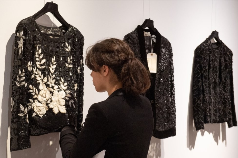 A woman examines a black and white appliqué jumper on show before the sale