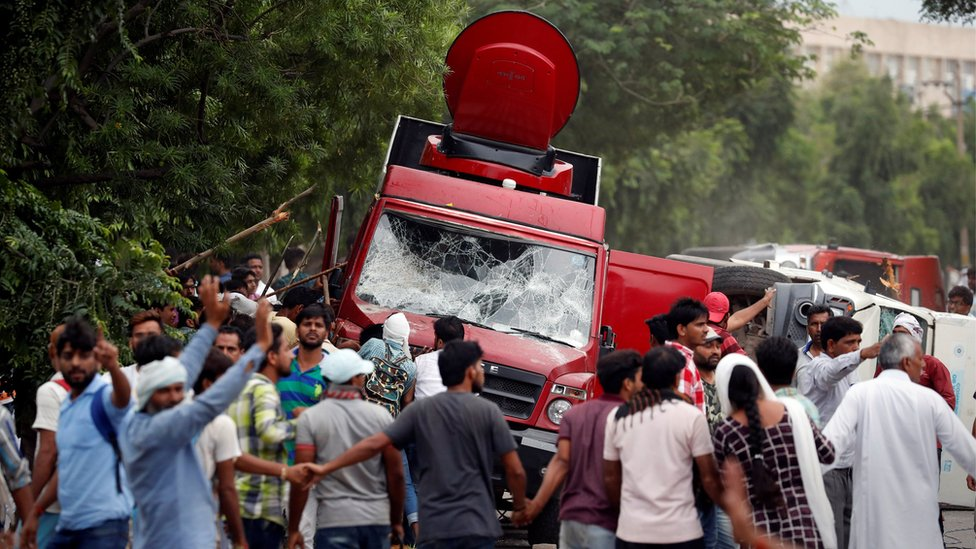 Rioters smash television trucks during violence in Panchkula, India, August 25, 2017