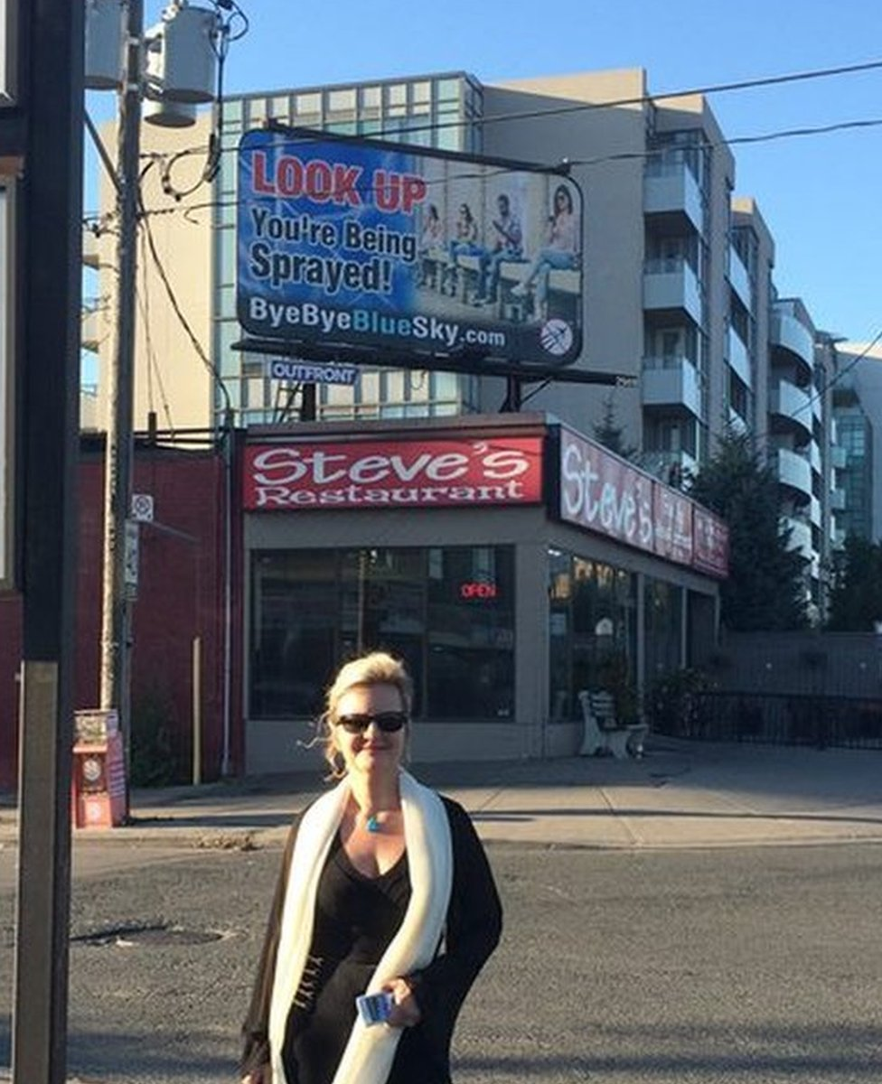 Suzanne Maher in front of a Bye Bye Blue Sky billboard in Toronto