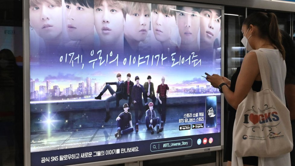 Seorang wanita berjalan melewati poster komersial yang menunjukkan anggota grup K-pop BTS di stasiun kereta bawah tanah di Seoul pada tanggal 1 September 2020. BTS telah menjadi artis Korea Selatan pertama yang menguasai chart single AS teratas