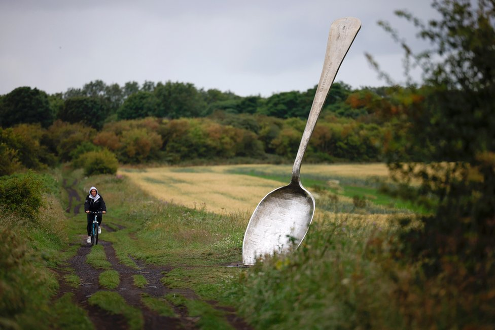 A person cycles past a large sculpture of a spoon on the edge of a field