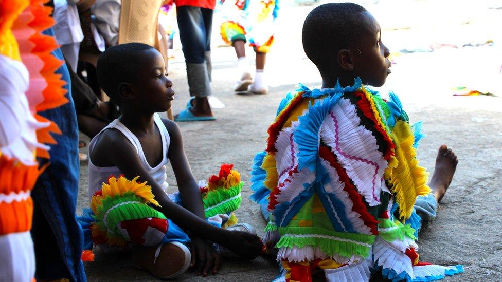 Children sit in multi-coloured outfits, made up of faux-feathers in Sekondi Ghana