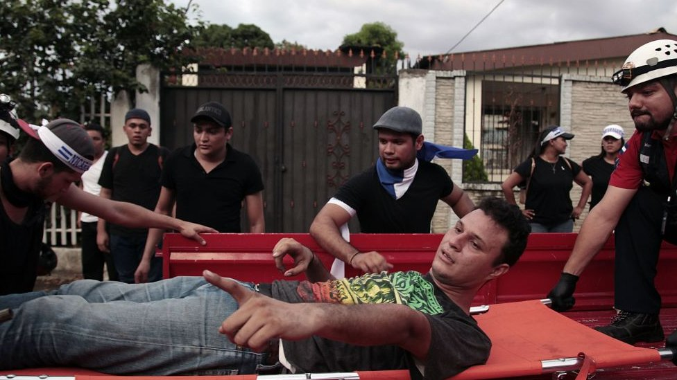 Un herido durante la marcha es evacuado en una camilla.