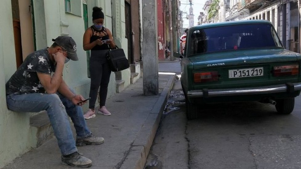 Cubans check their phones as telephone and internet connections were knocked out in a nationwide failure, in Havana, Cuba February 12, 2021
