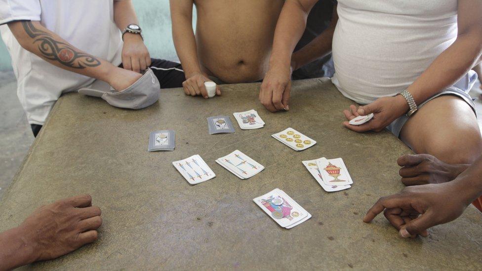Hombres y un niño juegan a las cartas en una estación migratoria