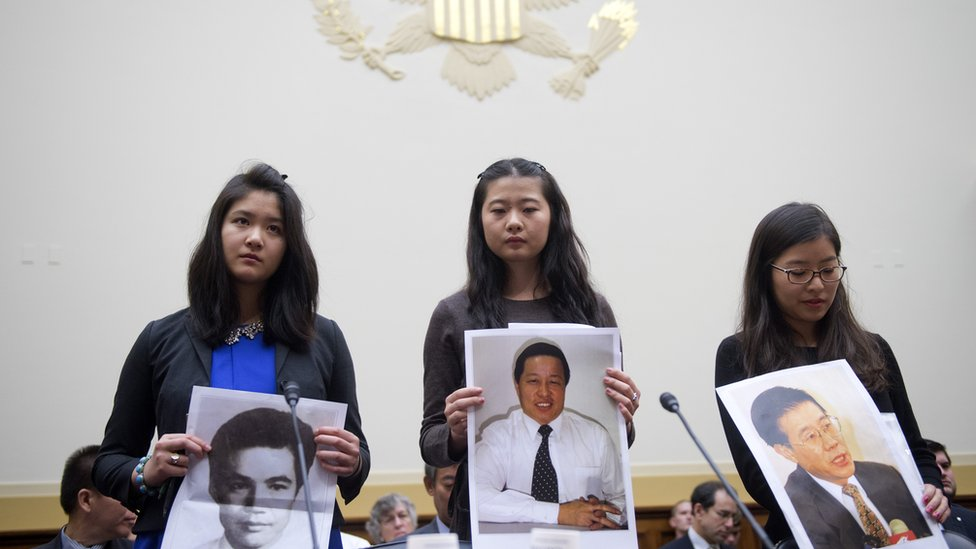 From left, Lisa Peng, daughter of Peng Ming, Grace Ge Geng, daughter of Gao Zhisheng, and Ti-Anna Wang, daughter of Wang Bingzhang, hold pictures of their imprisoned fathers