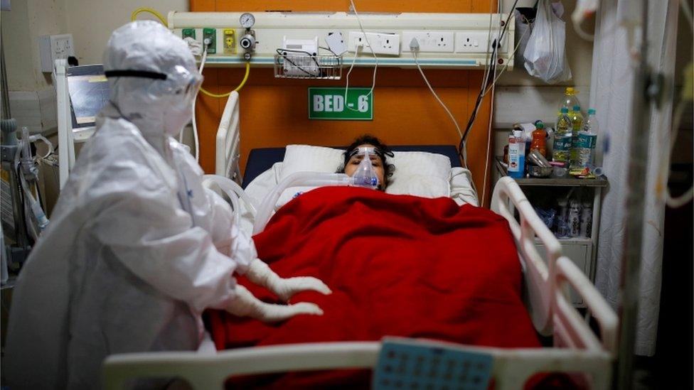 Woman in hospital bed with doctor in PPE