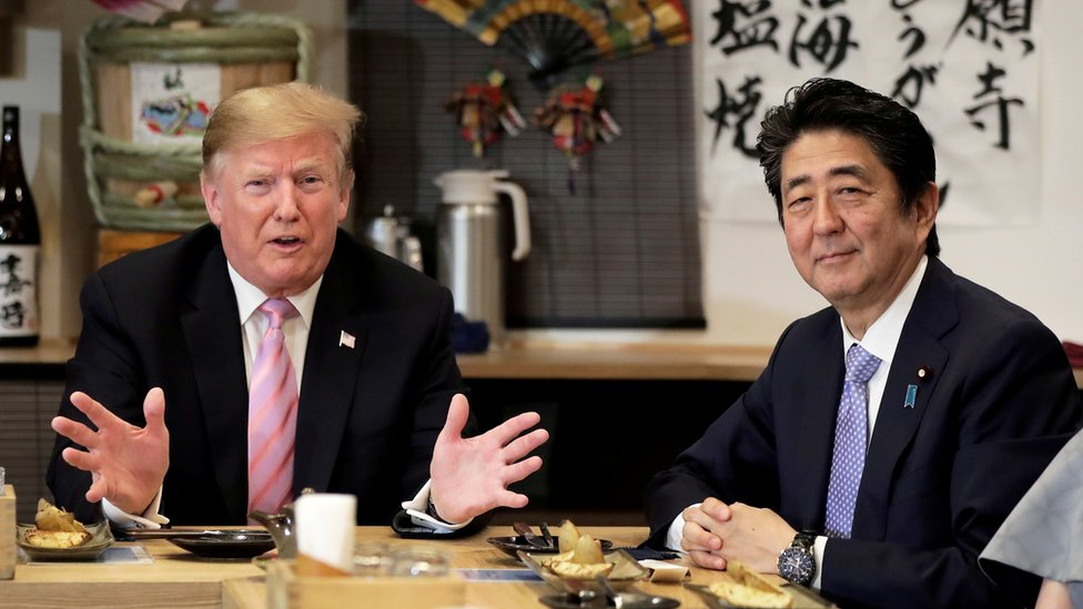 """U.S. President Donald Trump talks with Japanese Prime Minister Shinzo Abe during a couples dinner with first lady Melania Trump and Abe""""s wife Akie in Tokyo"""