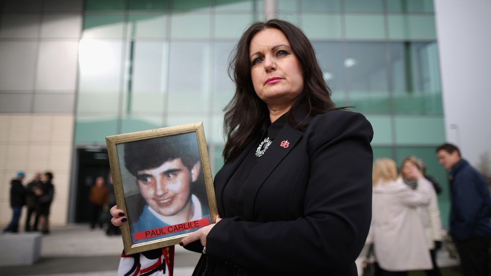 Donna Miller holding a picture of her brother, Paul Carlile