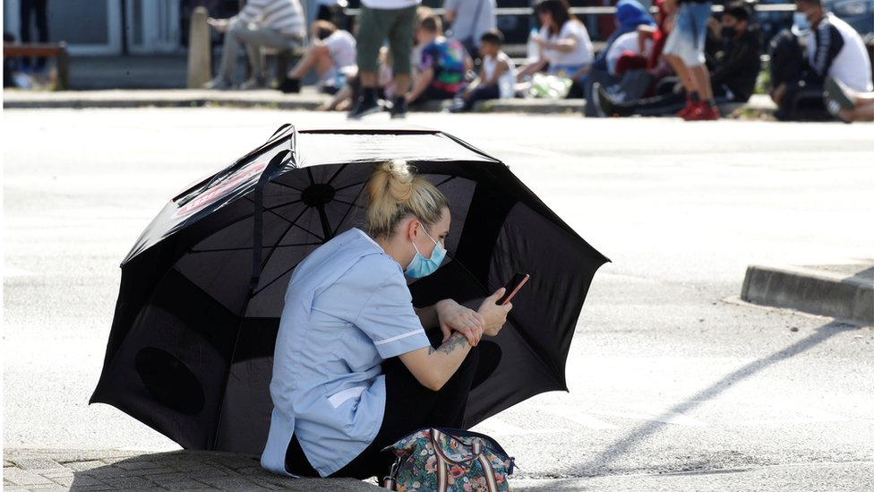 A woman uses an umbrella to shelter from the sun as she waits for a Coronavirus test outside a community centre following the outbreak of the coronavirus disease (COVID-19) in Bury