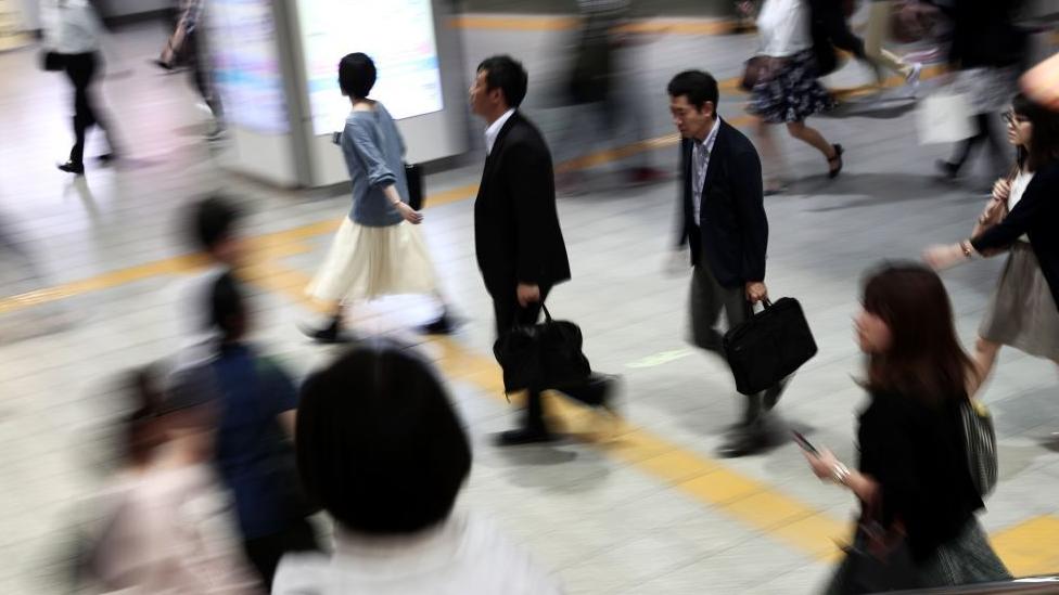 Orang-orang berjalan di stasiun kereta Jepang