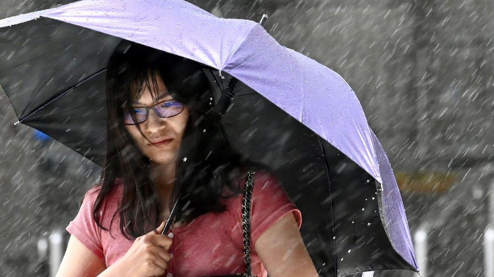 A woman shields herself with an umbrella as she walks in New Taipei City in rain brought by Typhoon Lekima as it passes northeastern Taiwan on August 9, 2019