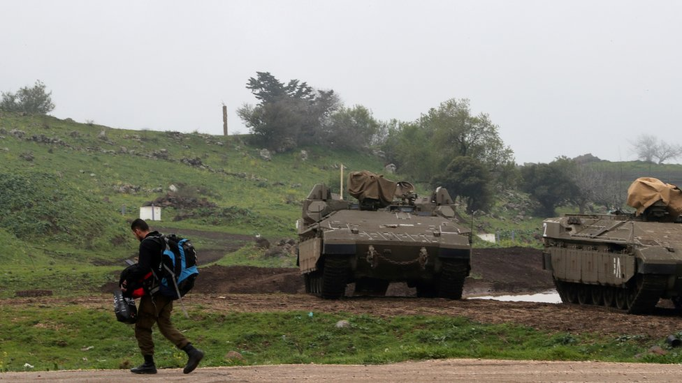 (أرشيف) جندي إسرائيلي بالقرب من مركبات عسكرية في مرتفعات الجولان المحتلة