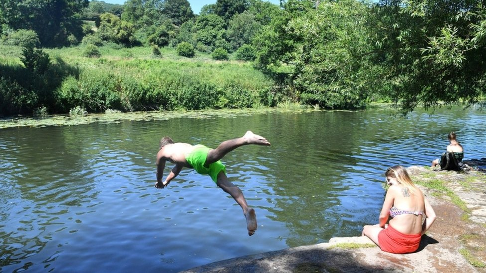 A man diving into the water at Warleigh Weir, near Claverton outside Bath