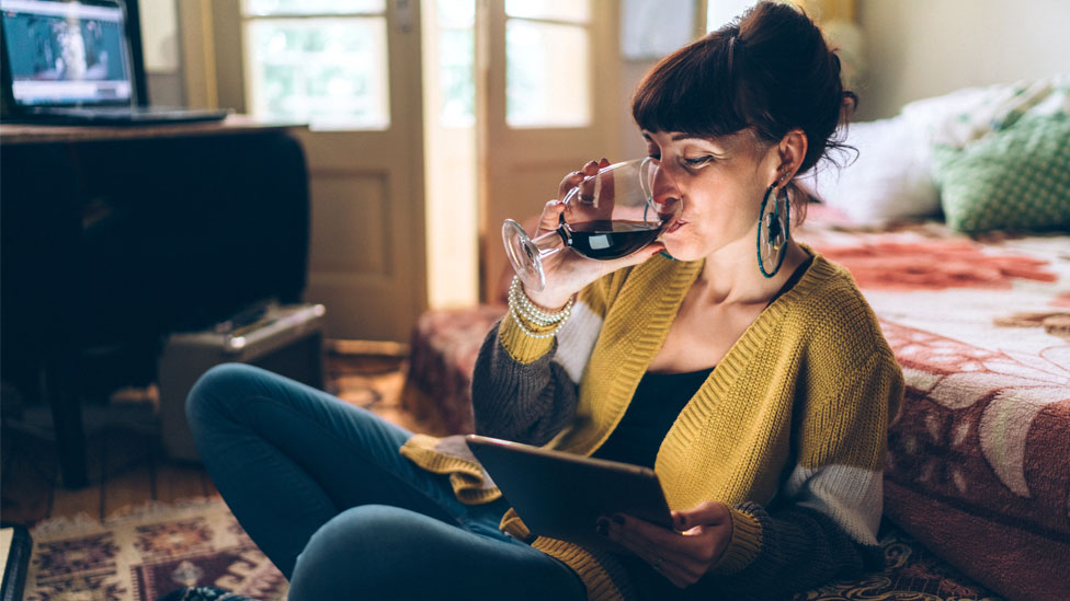 A woman drinking at home