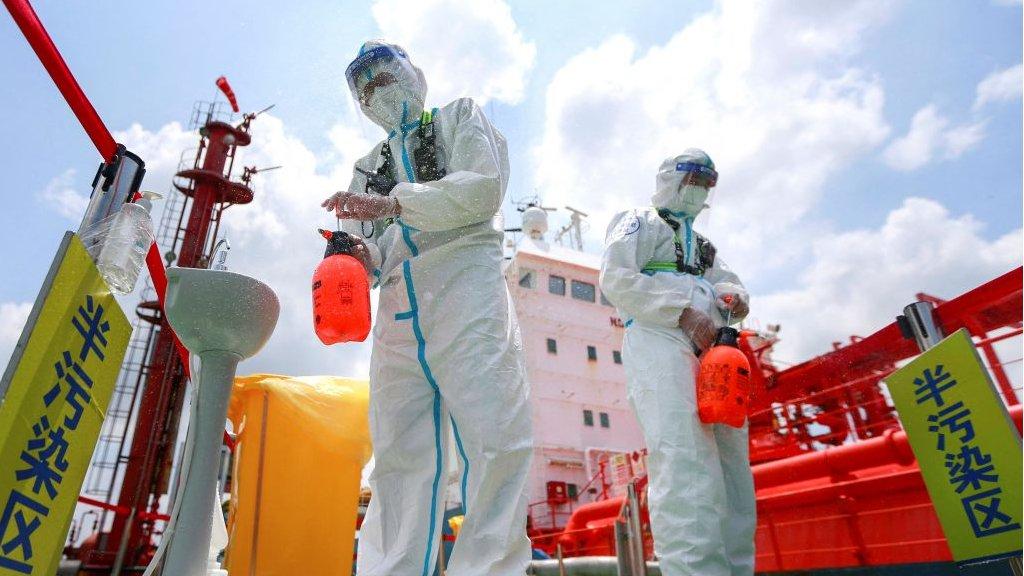 Policiais usando equipamentos de proteção contra a disseminação do desinfetante em spray no porto de Nanjing, na província de Jiangsu, no leste da China, em 4 de agosto de 2021.