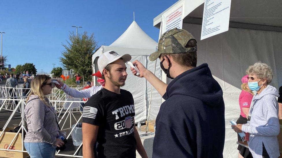 Un joven se toma la temperatura en Mosinee antes de un rally de Trump.