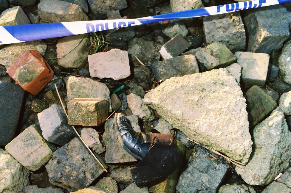 Boot on rocks with police tape next to it