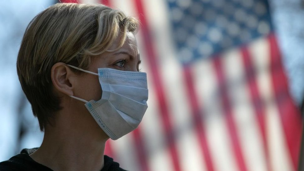 A woman wearing a mask stands in front of a US flag