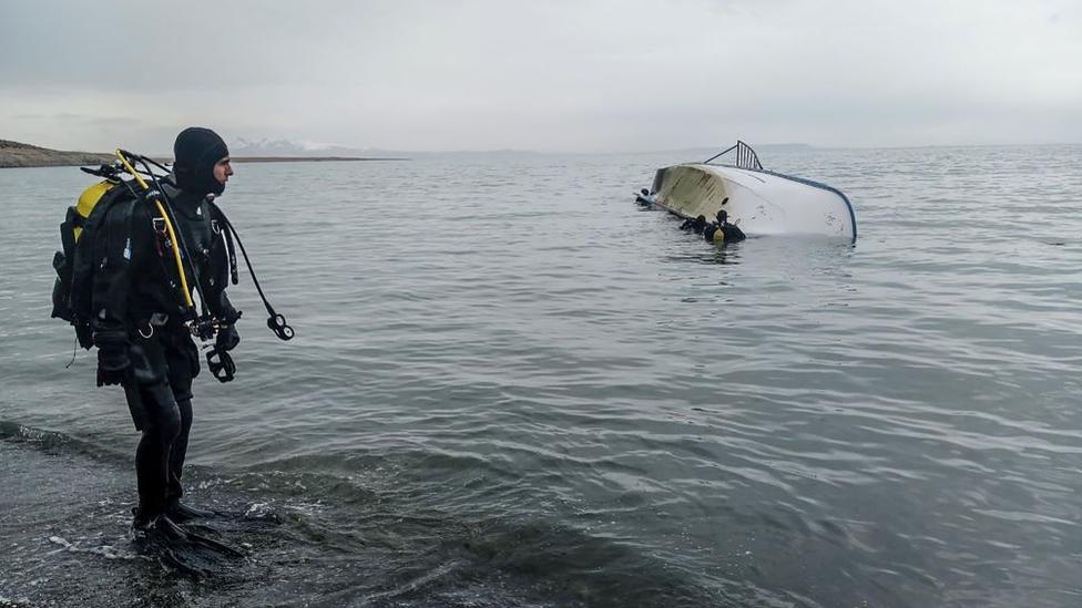 Un buzo mira a sus colegas en el agua por un bote volcado