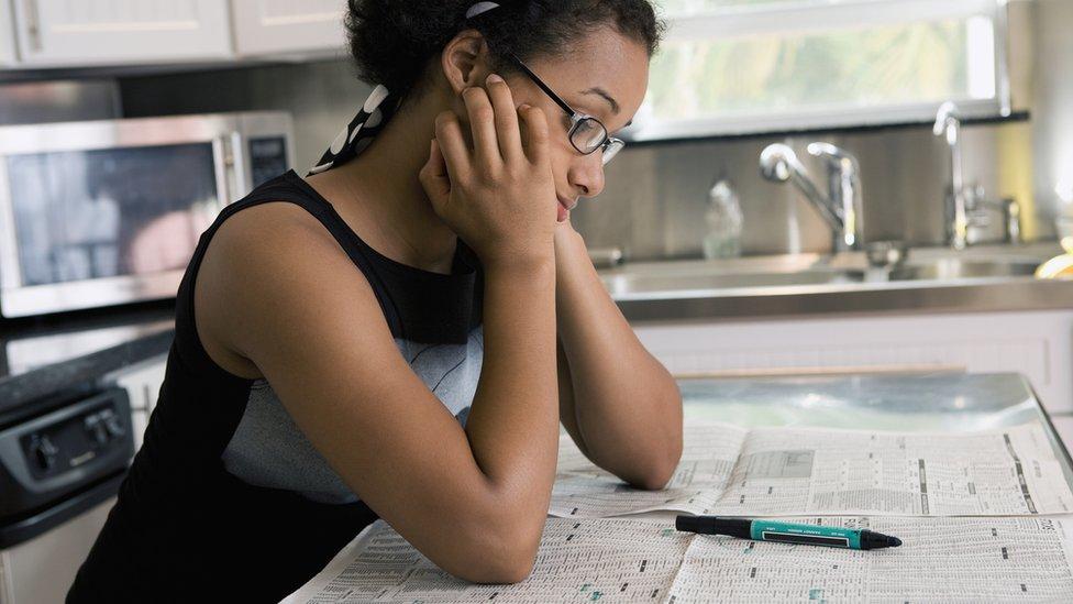 Una mujer mirando anuncios en el periódico