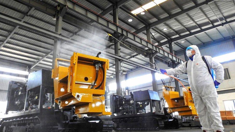 Un trabajador desinfectando máquinas antes de que sus colegas se reincorporen.