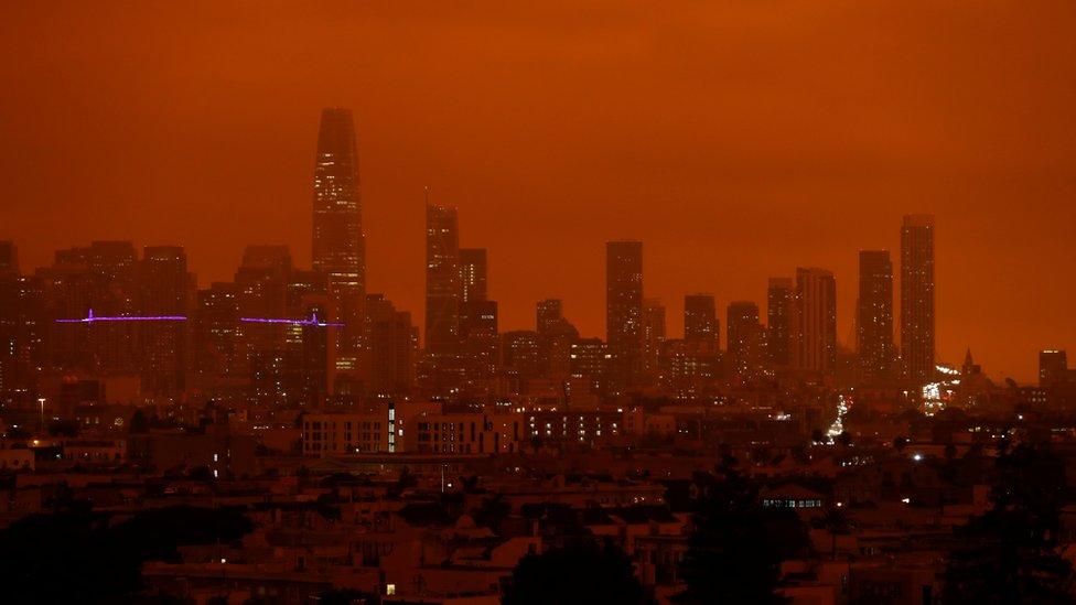 Prédios da cidade de São Francisco banhados por uma luz vermelha e fosca