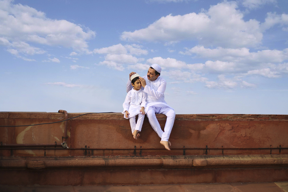 A father and son sitting in white traditional attire with blue sky behind