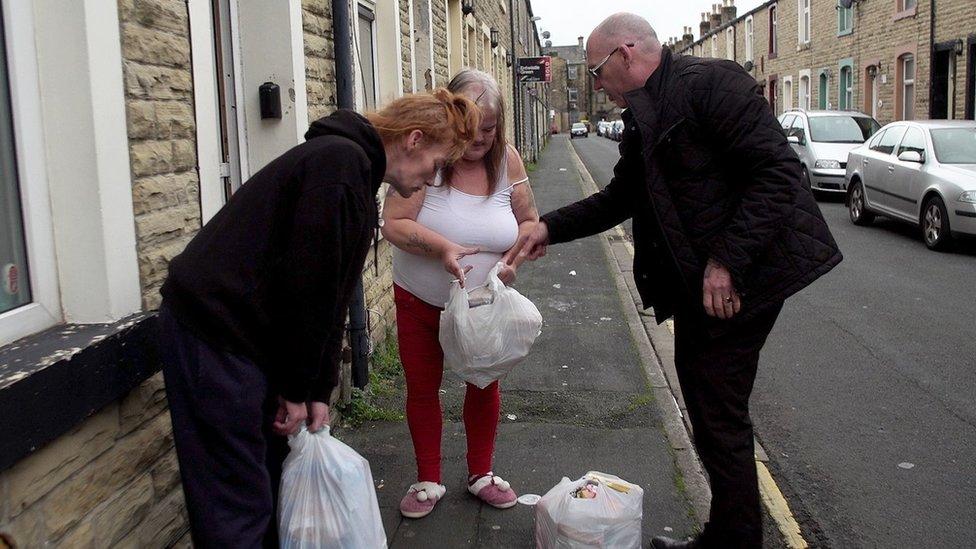 Mick Flemign distribuyendo bolsas de comida.