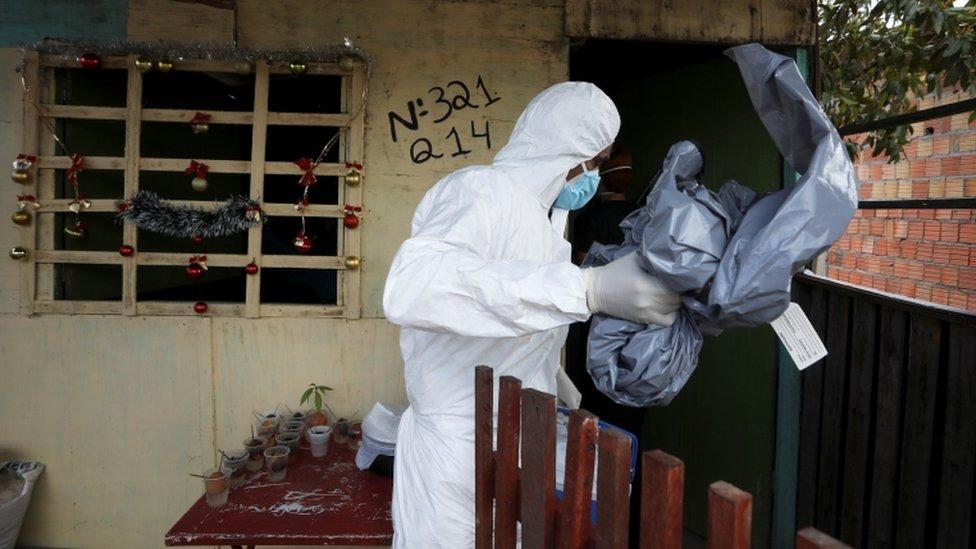 Profissional de saúde carregando saco usado para colocar corpo de pessoa morta com suspeita de covid em Manaus