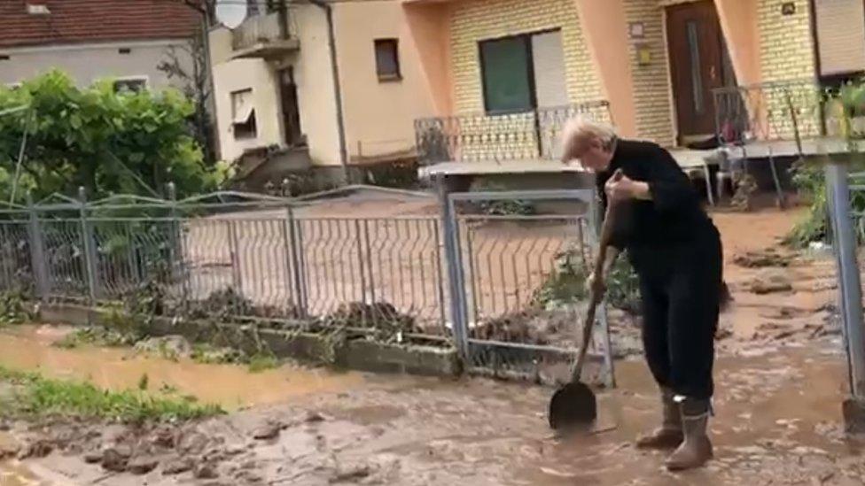 Žena lopatom čisti blato od poplava ispred kuće.