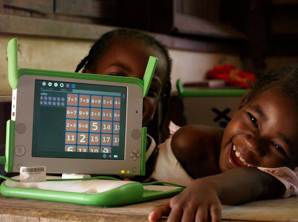 Madagascar, 2010. Children hold their laptops whilst smiling.to deploy small laptops in