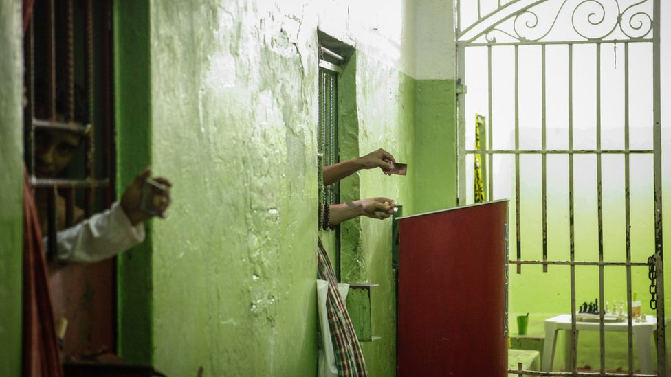 Inmates use mirrors to view visitors from their cells in the aging Desembargador Raimundo Vidal Pessoa penitentiary, inaugurated in 1904, on February 17, 2016 in Manaus, Brazil.