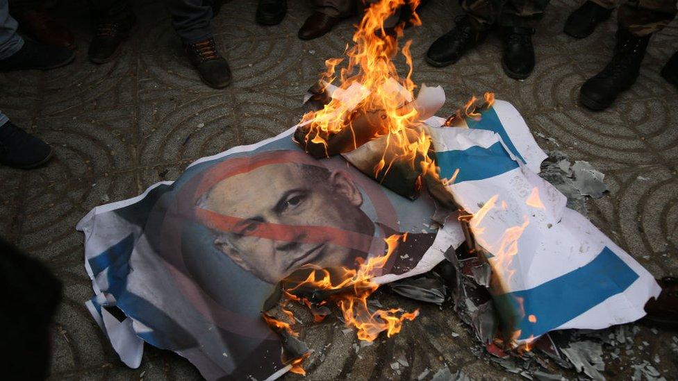 Pancarta con el rostro de Netanyahu quemándose