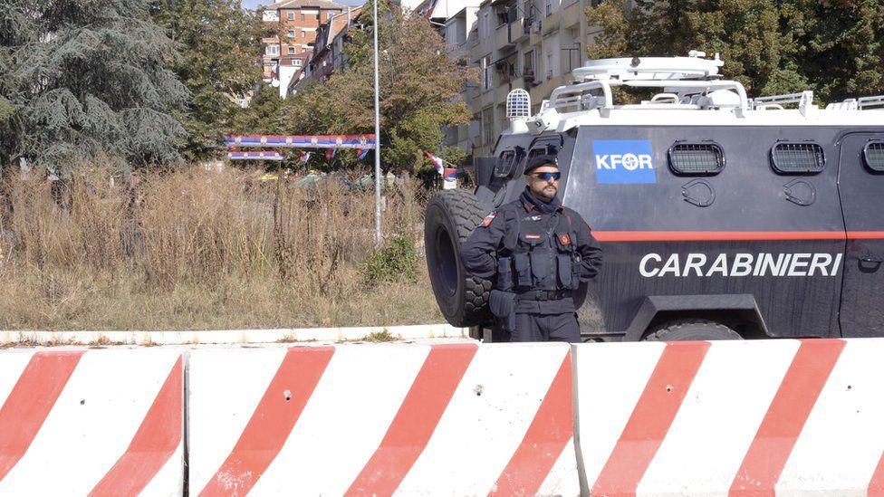 Vojnik Kfora ispred oklopnih vozila na mostu u Mitrovici na Kosovu