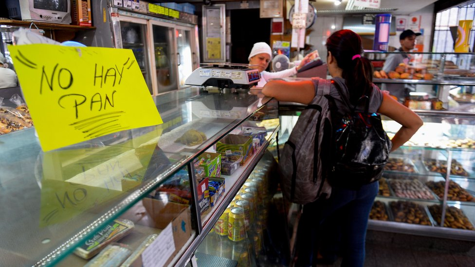 A woman waits at a bakery displaying a sign reading 'No Bread', in Caracas on February 25, 2016.