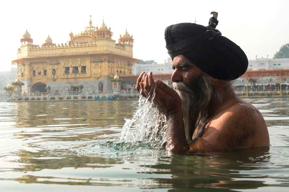 A Sikh devotee stands in water and splashes it on his face