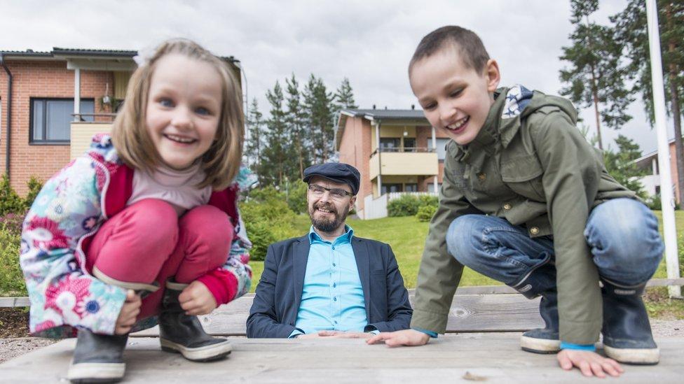 Padre con niños jugando.
