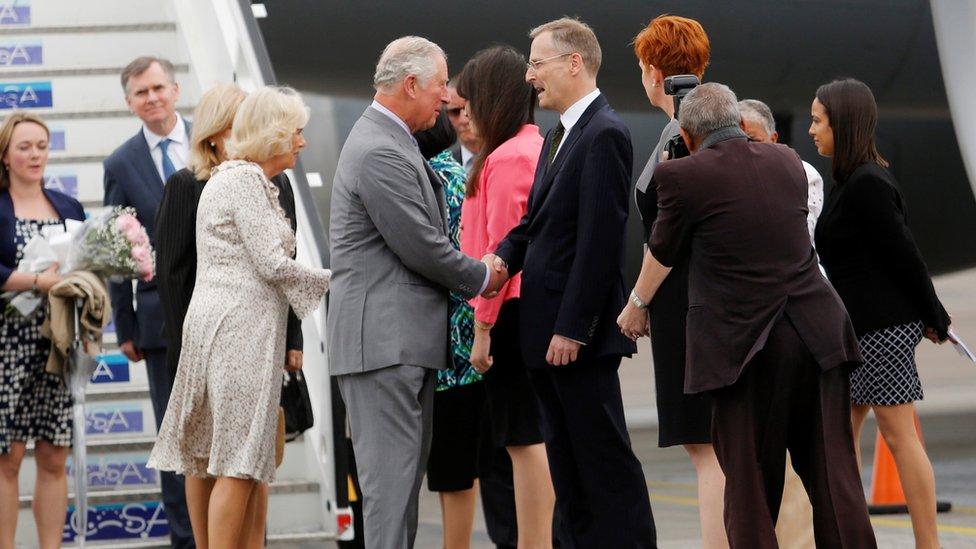 El príncipe Carlos y la duquesa de Cornualles dándose la mano con autoridades cubanas.