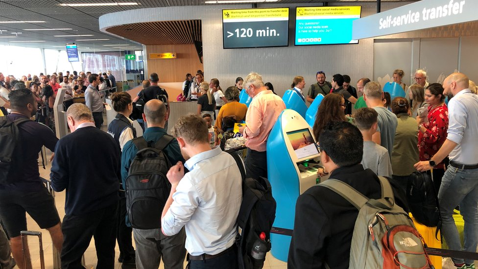 Passengers and staff wait for updates at Amsterdam's Schiphol airport on 24 July 2019