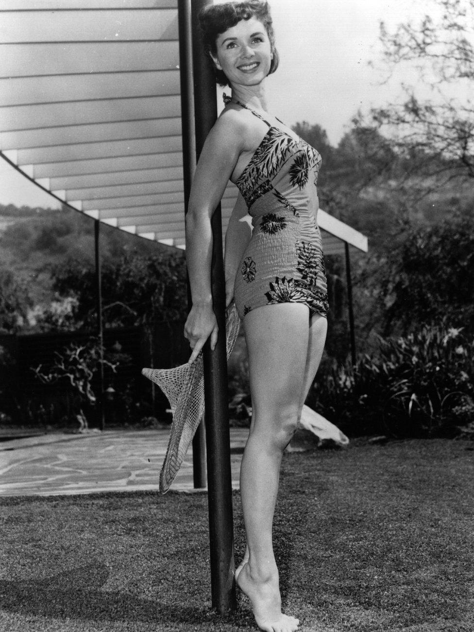 American actress, Debbie Reynolds modelling a swimsuit in the garden. Original Publication: