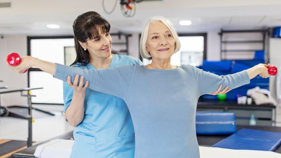 Una mujer mayor realiza un ejercicio con pesas bajo supervisión de una entrenadora